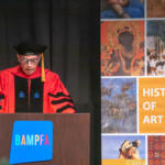 Professor Whitney Davis stands at a lectern during commencement proceedings
